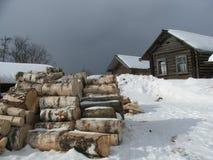 木房子多雪的村庄的冬天 免版税库存图片