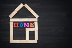 木房子由与家庭题字的玩具块做成在黑暗的木背景 复制空间 库存图片
