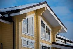 木房子的有双重斜坡屋顶的房屋窗口  库存图片