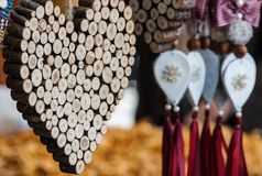 木手工制造心脏装饰品,与土气垂悬的装饰品在背景中,在销售中 房子或礼物的装饰 免版税库存图片