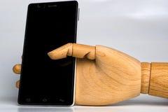 木手紧固了一个黑手机 免版税图库摄影