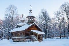 木教堂在日落的多雪的冬天森林里 库存图片
