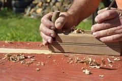 木整平机,从老木头,一种自然建筑材料,被手工造的木头,古老手工具的桌,执行木匠业, 库存照片