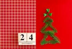 木日历与12月24日在红色背景的日期 新年和圣诞节概念,假日装饰 免版税图库摄影