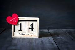木日历与2月14日,纸心脏和礼物日期  在与拷贝空间的黑暗的木背景 免版税库存图片