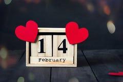 木日历与2月14日,纸心脏和礼物日期  在与拷贝空间的黑暗的木背景 免版税图库摄影