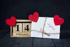 木日历与2月14日,纸心脏和礼物日期  在与拷贝空间的黑暗的木背景 免版税库存照片