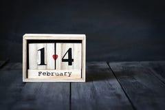 木日历与2月14日,纸心脏和礼物日期  在与拷贝空间的黑暗的木背景 图库摄影