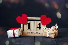 木日历与2月14日,纸心脏和礼物日期  在与拷贝空间的黑暗的木背景 库存图片