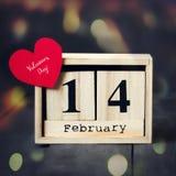 木日历与2月14日,纸心脏和礼物日期  在与拷贝空间的黑暗的木背景 库存照片