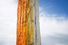 木杆绘了在为停住在海边的小船使用的夏天天空的桔子 免版税图库摄影