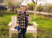 木材加工 盔甲的愉快的男孩与做雀鳝的螺丝刀 免版税图库摄影