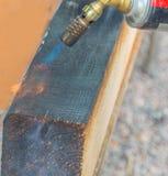 木材对待与从煤气喷燃器的火 免版税库存图片