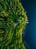 木村庄鸟瞰图在蓝色湖的绿色森林里在农村夏天芬兰 免版税图库摄影