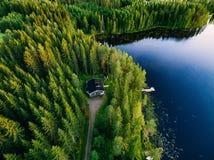 木村庄鸟瞰图在蓝色湖的绿色森林里在农村夏天芬兰 免版税库存照片