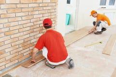 木条地板工作者在地板工作 免版税图库摄影