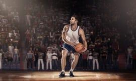 木条地板的蓝球运动员与在光线的球 图库摄影
