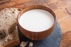 木杯子在厨房圆的板岩的牛奶和面包切片上 图库摄影