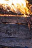 木板和叶子在火 免版税库存照片