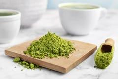 木板和瓢用搽粉的matcha茶 免版税库存图片