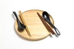 木板材或盘子有筷子和匙子的隔绝了白色背景 库存图片