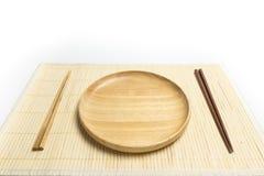 木板材或盘子有筷子地方的一张竹席子的隔绝了白色背景 库存照片