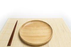 木板材或盘子有筷子地方的一张竹席子的隔绝了白色背景 免版税图库摄影
