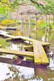 木板条桥梁、yatsuhashi和鲤鱼鱼在日本庭院里 免版税库存照片