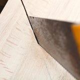 木板条用引形钢锯切开 库存照片
