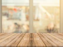 木板空的桌迷离在咖啡店背景中-能为显示或蒙太奇使用您的产品 免版税库存照片