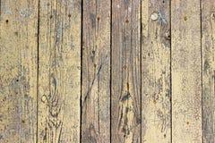 木板背景有破裂的芥末颜色油漆的 库存图片