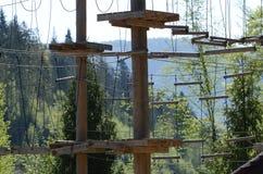 木柱子和一个绳索公园的垂悬的绳索绿色森林背景的在喀尔巴汗 乌克兰 图库摄影