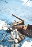 木柴和轴在烤肉附近 男孩节假日位置雪冬天 免版税库存图片