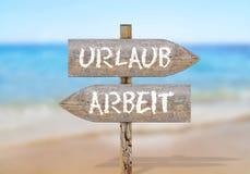 木标志措辞Arbeit和Urlaub,翻译:工作和Vacat 库存照片