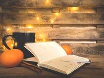 木桌、黄色聚光灯、普通话、桔子、桂香、热的茶黑盖帽和笔记本 库存图片