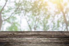 木桌前景有迷离绿色森林背景 免版税库存图片