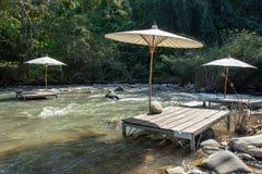 木桌和伞在小河在王楠Pua,南 免版税库存照片