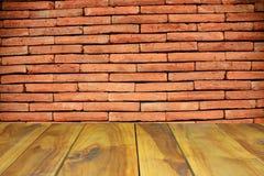 木桌和抽象红砖围住背景 免版税库存照片