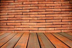 木桌和抽象红砖围住背景 免版税图库摄影