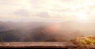 木桌和早晨山背景 库存照片