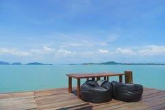 木桌和棕色椅子有海滩正面图-完善 库存照片