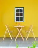 木桌和椅子与黄色墙壁 库存照片
