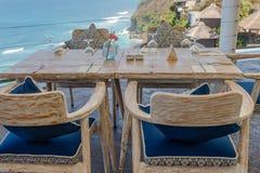 木桌和椅子在一个室外峭壁咖啡馆 免版税库存照片