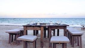 木桌和椅子在海滩 lounging的家具  图库摄影