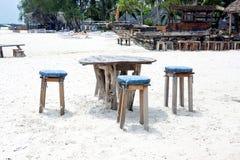 木桌和椅子在海滩 lounging的家具  库存照片