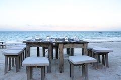木桌和椅子在海滩 lounging的家具  免版税库存图片