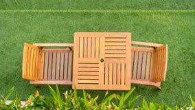 木桌和椅子桌在草 免版税库存图片