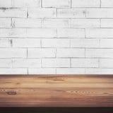 木桌和白色砖墙背景纹理 图库摄影