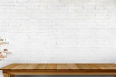 木桌和白色砖墙 免版税库存图片