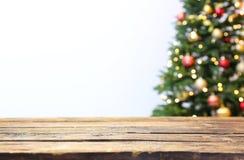 木桌和被弄脏的圣诞树与彩色小灯 库存图片